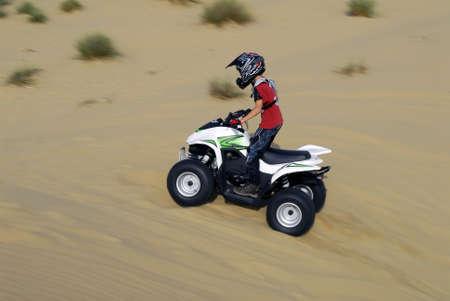 moto da cross: Young boy, guidando la sua moto quad nel deserto Archivio Fotografico