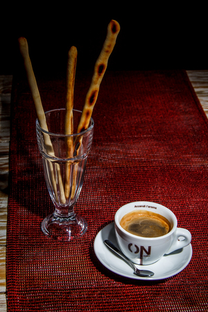 White cup of coffee on saucer with baked sticks in glass on rustic textured red tablecloth. Dark theme, vertical orientation.