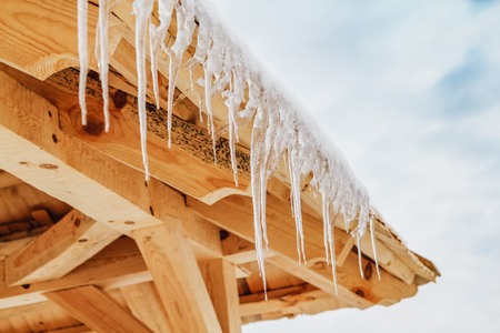 Thawing icicles with water drops falling against blue skies on the wooden roof at the end of winter. Spring is comming concept. Stock Photo