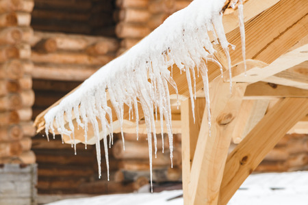 Many beautiful icicles melt on the wooden roof at the end of winter and water drops are fall down. Spring is comming concept.