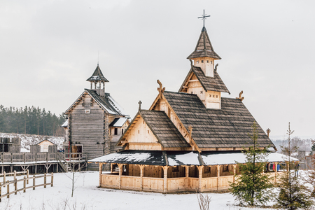 Ancient wooden Slavic church on a snowy landscape. Historical and Architectural Museum in the open air. Kiev, Ukraine, Ancient park Kievskaya Rus. Stock Photo