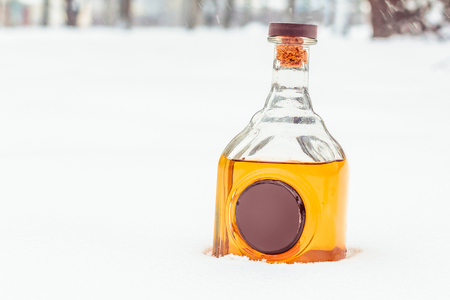 Glass bottle with hard alcohol and wax seal in the snow. Ukrainian luxury vodka.