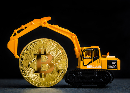 Bitcoin cryptocurrency mining concept. Miniature excavator holding golden bitcoin. Blockchain technology. Miniature excavator with Bitcoin golden coin. Dark background with copy space. Zdjęcie Seryjne