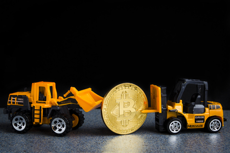 Bitcoin cryptocurrency mining concept. Blockchain technology. Models of industrial machines with bitcoin. Dark background with copy space.