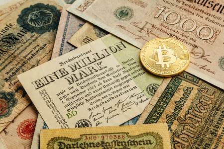 One physical Bitcoin coin with many old german money. Inflation 1923, one million marks is nothing. Cryptocurrency and Blockchain concept background. Close-up, copy space. Stockfoto