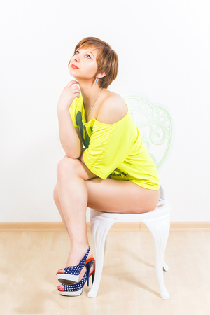 Portrait of a pensive caucasian girl wearing yellow T-shirt with naked shoulders and legs, sitting on chair over white background.
