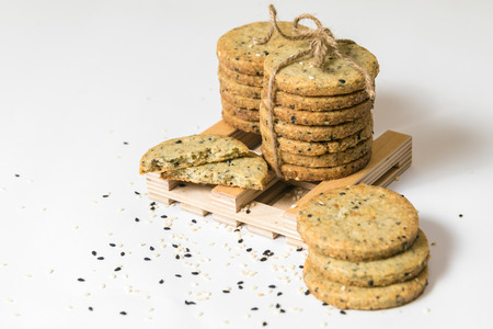Sesame cookies pile with rustic twine isolated on white background. Copy space.
