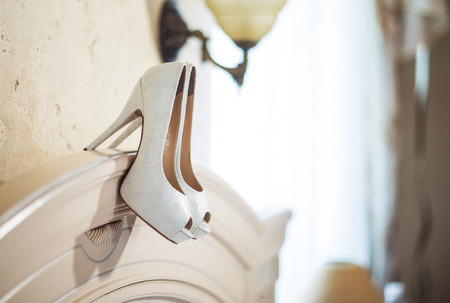 white bride shoes hanging on the back of the bed in the room Stock Photo