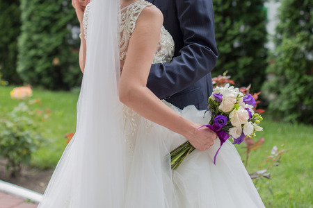 bride and groom hold hands in the park
