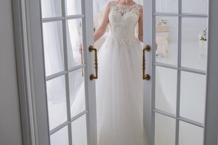 the bride wedding dress stands next to the door
