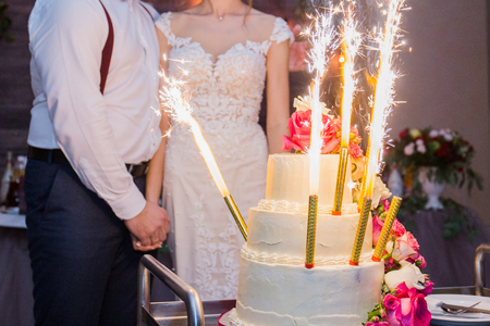 fireworks in a wedding cake on the background of the newlyweds Фото со стока