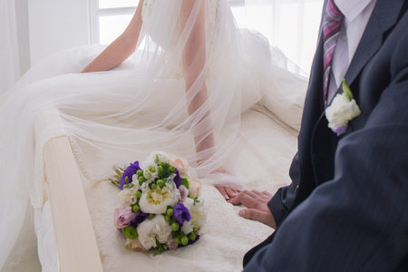 bride and groom sit together on the bed