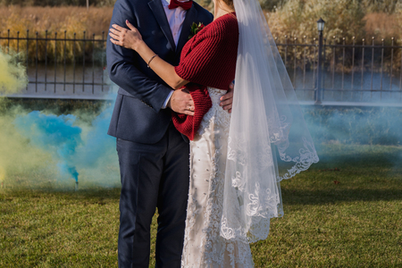 colorful smoke behind the newlyweds in the park