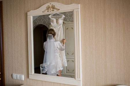 bride in bathrobe holding wedding dress in hands Stok Fotoğraf