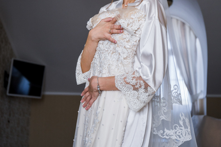 bride in bathrobe holding wedding dress in hands Stock fotó