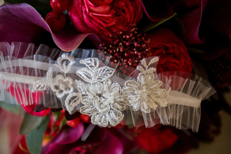 the garter of the bride lies on a wedding bouquet