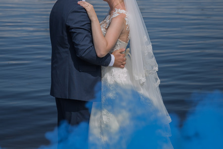 bride and groom stand together against the water