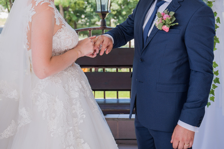 bride and groom wear rings at the ceremony