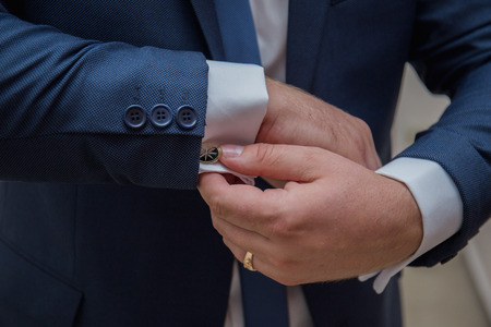 the groom fastens the cuffs of the sleeves on the shirt Stock Photo