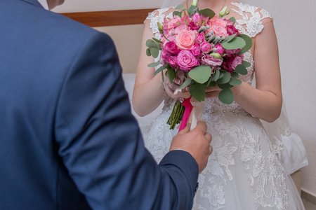 groom in suit holds the bridal bouquet Stockfoto