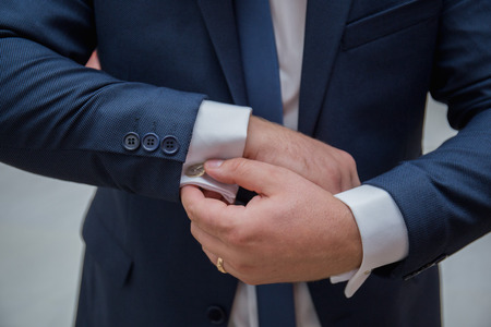 the groom fastens the cuffs of the sleeves on the shirt