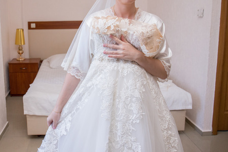 bride in dressing gown and wedding dress in hands