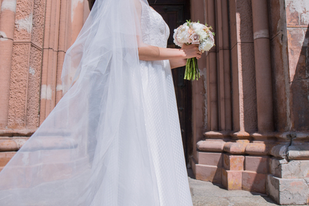 bride with wedding bouquet and veil near the church
