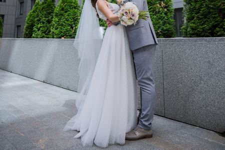 The bride and groom are standing together near the office building.