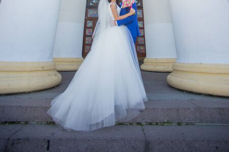bride and groom near building with columns