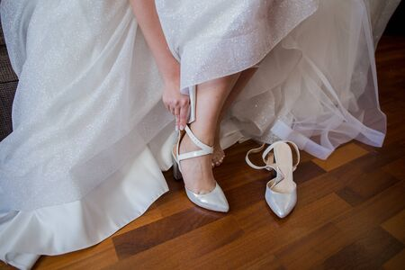 the bride puts shoes on her feet