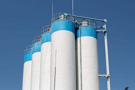 a tall factory barrels and blue sky Foto de archivo - 150127863