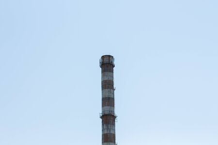 a factory chimney against blue sky Фото со стока