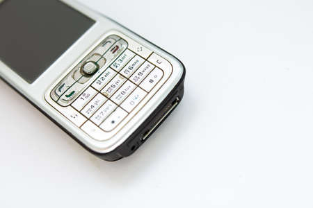 old push-button smartphone on white background