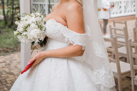 bride in a wedding dress and phone in her hands Stock Photo