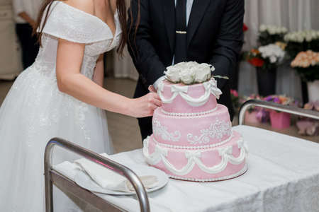 the groom and bride cut the wedding cake