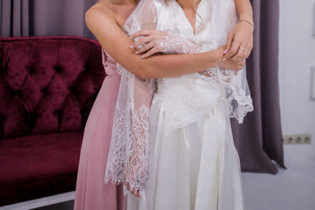 a bride in peignoir with bridesmaid in studio