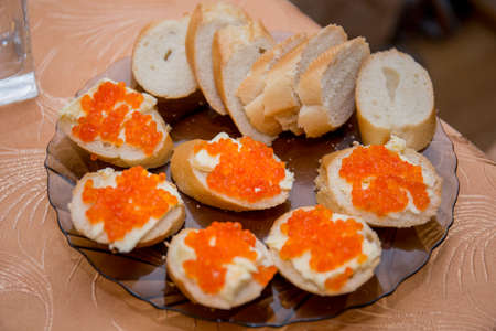 sandwiches with red caviar on kitchen table
