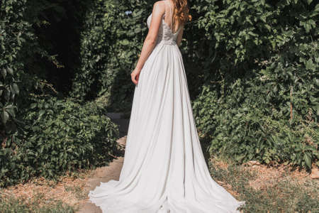 bride in a wedding dress whirls in park