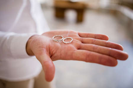 a wedding rings in the palm of the groom
