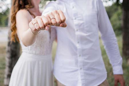 bride and groom show rings on their hands