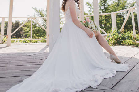 the bride in a wedding dress sits on a bench