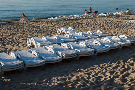many sun loungers on beach early in the morning Фото со стока