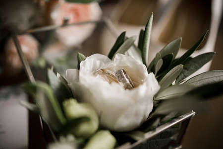 a wedding rings in a glass box with a flower