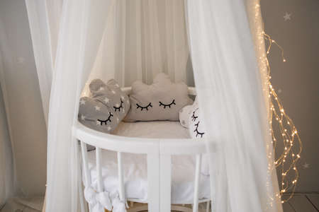 a baby cot with fabric top and garland