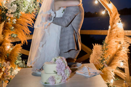 a bride and groom near wedding arch with cake