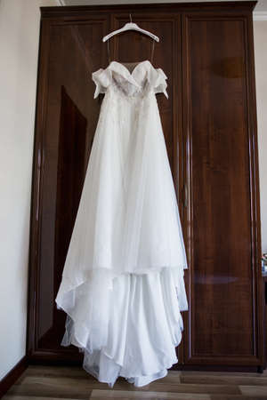 a bride's wedding dress hanging on the wardrobe
