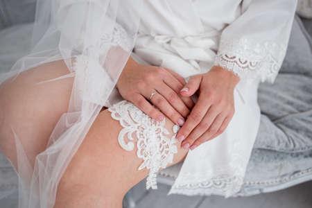 the bride puts a garter on her leg in morning Stok Fotoğraf