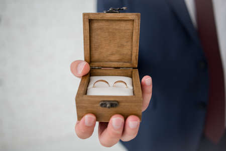 wooden box for wedding rings in the hands of groom