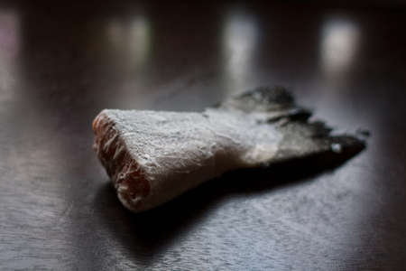 frozen salmon tail on dark kitchen table Фото со стока