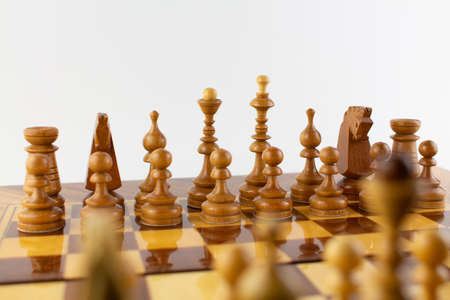 a chessboard made of wooden pieces on white Imagens